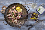 Fried octopus with tzatziki and kalamata olives as top view in an iron pan - 175089435