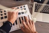 Musician is recording tunes on his computer with MIDI controller. first-person view