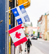 Closeup of two small Canadian and Quebec flags hanging on restaurant on Saint Louis street in old town road