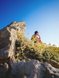 Frau sitzt in der Natur auf einem Felsen - 175110218