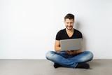mann sitzt auf dem boden mit seinem laptop - 175114844
