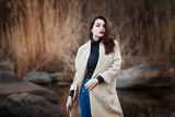Portrait of a Stylish Pretty Young Woman in Autumn Fashion Coat walking outdoors. - 175126408