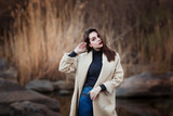 Portrait of a Stylish Pretty Young Woman in Autumn Fashion Coat walking outdoors. - 175126424