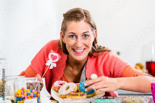 Portrait of woman holding heart shape lollipop looking into camera Poster