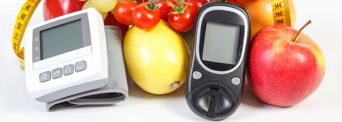 Glucometer for checking sugar level, blood pressure monitor, fruits with vegetables and centimeter, healthy lifestyle