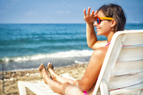 Beauty Fashion model on resort beach. Young woman on sea beach. Summer vacation on tropical beach on sunny day