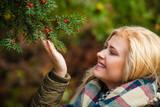 Woman dressed warmly looking at bush - 175164487