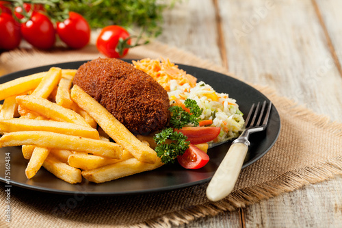Staande foto Kiev Chicken Kiev (de Volaille chop) with french fries and salads.