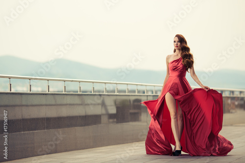 Plakát Beautiful woman in red fluttering dress. Urban background.