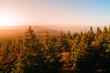 Autumn haze illuminated by sun above mountain peaks, Eagle Mountains, Orlicke hory, Czech Republic.
