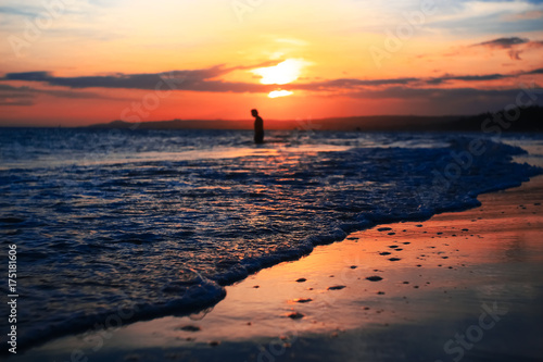 Foto op Canvas Zee zonsondergang A man walking on the beach