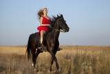 Blonde in red dress galloping on horseback along a country road - 175182662