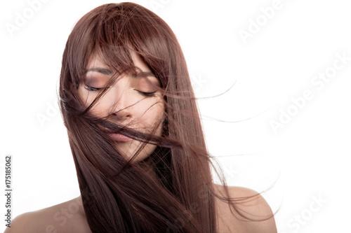 Brunette lovely girl. Healthy long hair flying over face