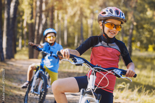 kids on abicycles in the sunny forest. children cycling outdoors in helmet
