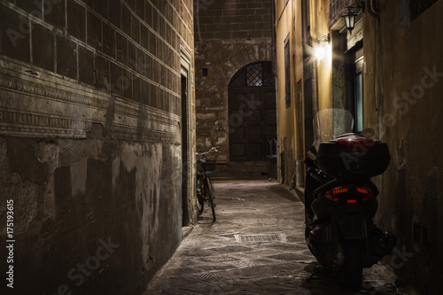 Papiers peints Florence Motorcycle and bicycle stand in a dark alley at night, Florence, Italy