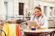 Young woman using digital tablet in cafe after shopping
