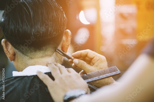 person man haircut getting stylish hair vintage shaving, , with razor by barber hairdresser with hands at barbershop Plakat
