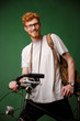 Young cheerful readhead bearded hipster with backpack and retro camera, standing on bicycle