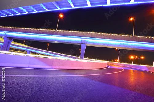Empty road floor with city viaduct bridge of neon lights night Poster