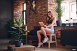 Attractive sporty female using tablet PC in loft interior room. - 175207210