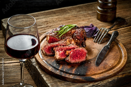 Fotobehang Steakhouse Grilled ribeye beef steak with red wine, herbs and spices on wooden table