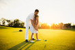 A man is teaching a girl who is preparing to make her first hitting with a golf club
