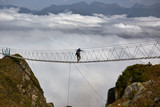 Man walking on suspension bridge and looking at cloudy mountains below. - 175238679