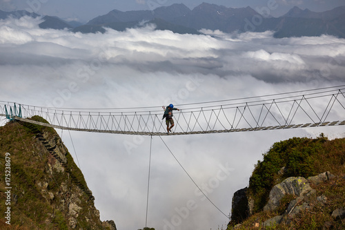Wall mural Man walking on suspension bridge and looking at cloudy mountains below.