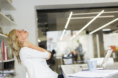 Fridge magnet Businesswoman in the office taking a break and doing a neck exercise