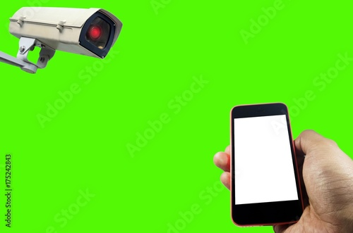 hand using smart phone with white screen monitoring and CCTV security indoor camera system operating isolated on green background for photo montage, surveillance security and safety technology concept - 175242843
