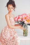 Beautiful young woman with big bouquet of peony - 175246085