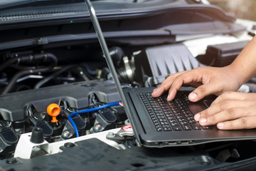 Detail of a mechanic using electrnoic diagnostic equipment to tune a car