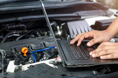 Detail of a mechanic using electrnoic diagnostic equipment to tune a car - 175246263