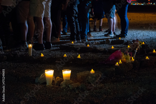 Rocks on the ground at a candlelight vigil spell out RIP. Poster