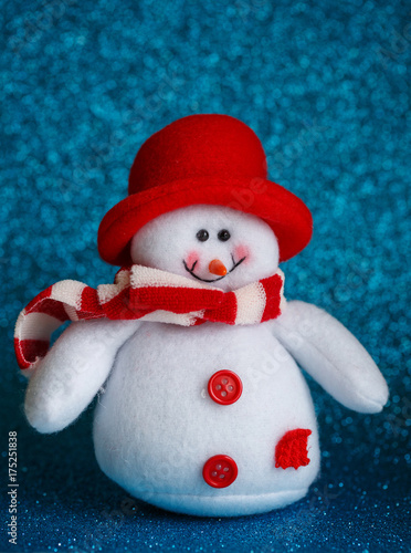 Smiling snowman toy dressed in scarf and cap on abstract bokeh background Poster