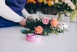 Self-employed young woman owner of florist shop arranging bouquet of roses - 175255084