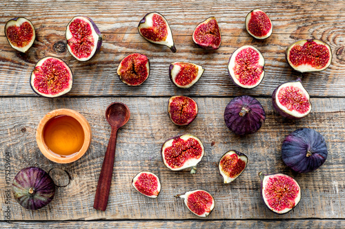 Wall mural Fresh blue figs and honey on wooden background top view
