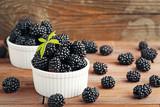 Ripe blackberries in bowls on wooden table - 175261443