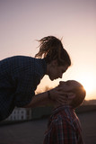 Gentle kissing couple on sunset backdrop closeup. Romantic date outdoors, hipsters in love in focus on foreground, feelings concept - 175268684