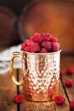 Fresh ripe raspberries in a copper mug - 175268814