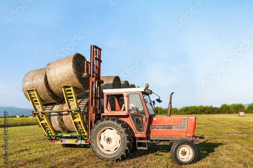 Fotobehang Trekker Tractor lifting hay bale on barrow.