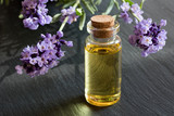A bottle of lavender essential oil on a dark background - 175275276