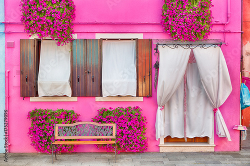 Pink house with pink flowers and plants. Nice bench under windows. Colorful house in Burano island near Venice, Italy