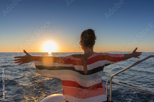 girl on the prow of a boat with sunset with open arms. Poster