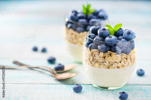 Fotobehang Fitness Homemade greek yogurt with granola and fresh blueberries in a jar with spoon on a wooden background, selective focus