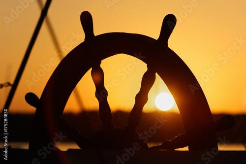 Fotobehang Schip Ship's wheel on sunset background.