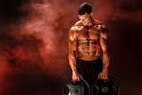 Very brawny guy bodybuilder. Bodybuilder with dumbbells in his arms on dark background with red smoke. - 175288050