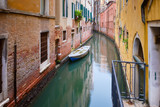Small boat on a narrow canal surrounded by old weathered buildings in Venice - 175292212