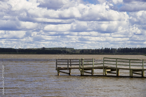 Aluminium Pier boats and dock on river very grown sky with clouds