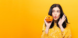 Young woman holding a pumpkin in halloween theme - 175294475